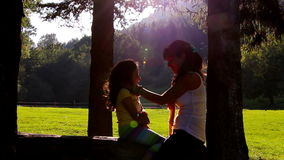 Mother and daughter hugging and kissing on tree log. Sunset in the background.  stock video footage