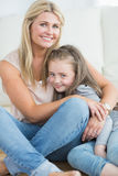 Mother and daughter hugging in living room Stock Photo