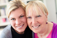 Mother and daughter hugging, looking at camera Stock Image