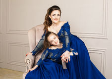 Mother and daughter hugging and looking at the camera. Happy loving family. Mother and daughter in beautiful long luxury blue dres Royalty Free Stock Photos
