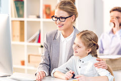 Mother and daughter hugging and looking on monitor in business office, father behind Royalty Free Stock Photos