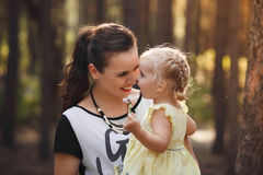 Mother and daughter hugging in love playing in the park. Warm sunny summer day stock images