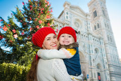 Mother and daughter hugging near Christmas tree in Florence. Smiling mother and daughter hugging in front of Christmas tree near Duomo in Florence, Italy. Modern stock photo