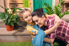 Mother and daughter hugging on porch with potted plants Stock Photo