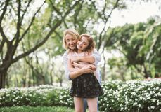 Mother and Daughter Hugging. Portrait of Young Happy Beautiful Mother and Daughter Hugging. Embrace in Sunny Day on Meadow Royalty Free Stock Image