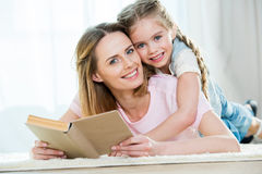 Mother and daughter hugging while reading book Royalty Free Stock Photography