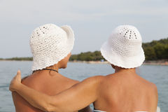 Mother and daughter hugging on sea shore, sunny beach Stock Image