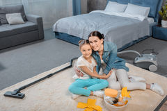 Mother and daughter hugging while sitting on carpet with cleaning supplies Stock Photo