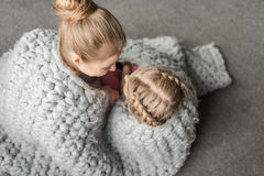 Mother and daughter hugging and sitting on floor with wool knitted blanket Royalty Free Stock Image