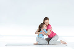 Mother and daughter hugging while sitting on yoga mat Stock Images