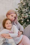Mother and daughter hugging sweetly. At Christmas Royalty Free Stock Image