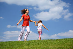 Mother with daughter hurry and play on grass. In day-time Royalty Free Stock Photo