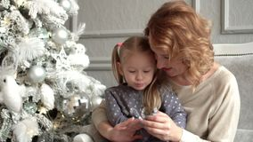 Mother with the daughter I consider Christmas balls sitting on a sofa at a fir-tree. Mother with the fair-haired. On this video you can see the girl at a stock video