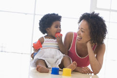 Mother and daughter indoors playing. And smiling