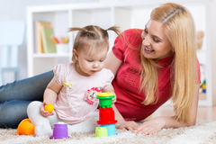 Mother and daughter indoors playing and smiling Stock Image