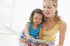 Mother and daughter indoors reading book Stock Photo