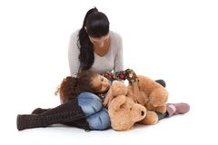 Mother and daughter intimate moments. Little daughter lying in mother's lap, hugging huge plush bear Royalty Free Stock Photo
