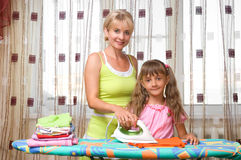 Mother and daughter is ironing Stock Images