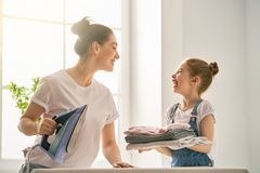 Mother and daughter ironing at home Stock Photo