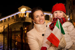 Mother and daughter with Italian flag in Christmas Venice, Italy Royalty Free Stock Photos