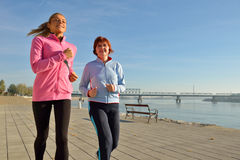 Mother and daughter jogging. On coasts stock image