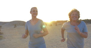 Mother and Daughter Jogging. Steadicam shot of young and mature women (or mother and daughter) jogging on the beach in the morning or evening stock video