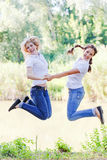 Mother and daughter jumped the river. Mother and daughter laughing, holding hands and having fun royalty free stock photo