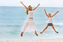Mother and daughter jumping on beach Royalty Free Stock Photos