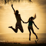 Mother and  daughter jumping on the beach Stock Image