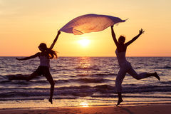 Mother and daughter jumping on the beach at the sunset time. Stock Photo