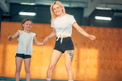 Mother and daughter jumping on trampoline and doing split stock photos
