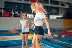 Mother and daughter jumping on trampoline and doing split stock images