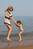 Mother and daughter jumping in the waves. A young beautiful mother and daughter jumping in the waves Stock Photo