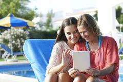 Mother and Daughter Skpying On Digital Tablet. Mother and Daughter keeping in touch with friends and family using a digital tablet while on holiday stock photos
