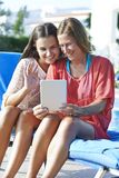 Mother and Daughter Skpying On Digital Tablet. Mother and Daughter keeping in touch with friends and family using a digital tablet while on holiday stock photography