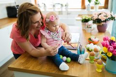 Mother and daughter kid painting easter eggs royalty free stock images