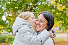Mother and daughter kiss in autumn Stock Photos