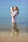Mother and daughter kissing. Beautiful girl modeling at the beach Stock Photos