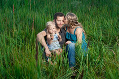 Mother and daughter kissing daddy outdoors royalty free stock photo