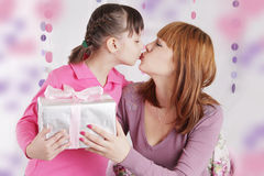 Mother and daughter kissing and holding present Stock Image