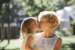 Mother and daughter kissing. Mother and daughter a kiss on the lips Royalty Free Stock Image