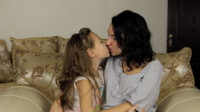 Mother and daughter kissing. Love. Happy cheerful family Mom and Baby girl smiling together and hugging at home.