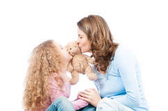 Mother and daughter kissing teddy bear. Stock Image