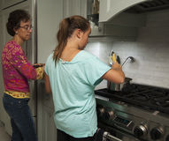 Mother and daughter in kitchen Stock Photos