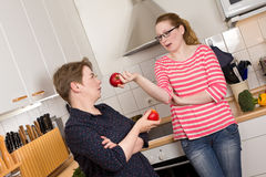Mother daughter kitchen apples discussion Royalty Free Stock Photo