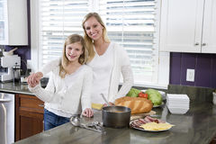 Mother and daughter in kitchen making lunch Stock Photo