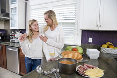 Mother and daughter in kitchen making lunch Stock Photos