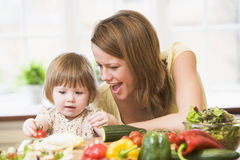 Mother and daughter in kitchen making a salad Royalty Free Stock Image