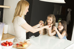 Mother and daughter in the kitchen. Mother and daughter in the modern kitchen prepating food stock photo