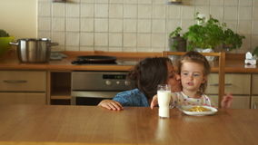Mother and daughter in the kitchen. Mom gives the girl milk. A good appetite. Healthy Eating stock video footage